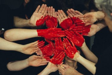 A group of Hands with a heart of love painted on them